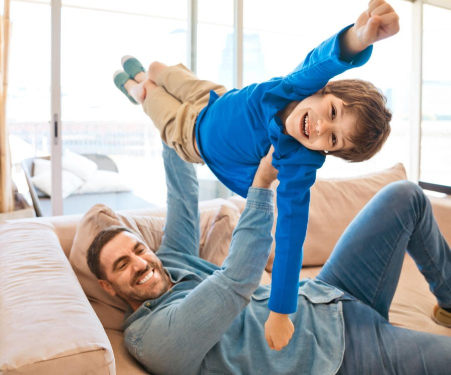 Father and son playing together on sofa in living room. Man lifting up his boy. Family staying at home due to pandemic COVID-19.